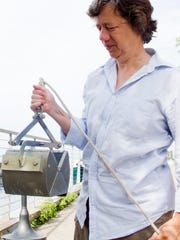 Ellen Marsden totes one of her favorite tools: a Ponar, used to retrieve samples from the lake bottom.