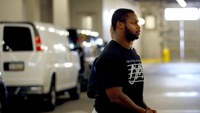 Phoenix police officers escort Arizona Cardinals running back Jonathan Dwyer, 25, to the 4th Avenue Jail following his arrest on suspicion of aggravated assault Wednesday, Sept. 17, 2014 in Phoenix, Ariz