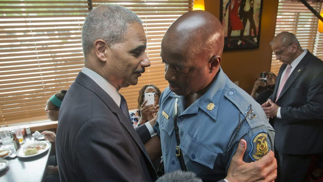 Attorney General Eric Holder talks with Capt. Ron Johnson of the Missouri State Highway Patrol at Drake's Place Restaurant in Ferguson, Mo., last month after the shooting Michael Brown by a police officer.