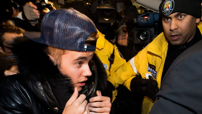 Justin Bieber is swarmed by media and police officers as he turns himself in to city police in Toronto on assault charges Jan. 29, 2014.