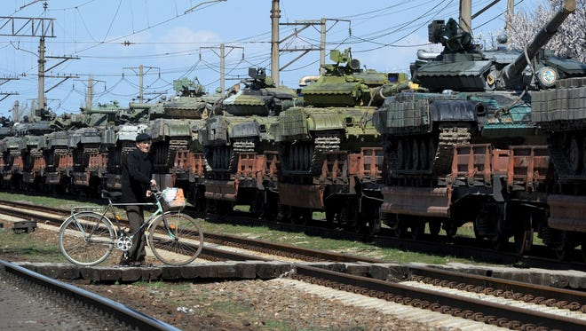 A man stands near a trainload of modified T-72 Russian tanks after their arrival in Gvardeyskoe railway station near the Crimean capital Simferopol, on Monday. The Crimean crisis has sparked the most explosive East-West confrontation since the Cold War and fanned fears in Kiev that Russian President Vladimir Putin now intends to push his troops into southeast Ukraine.