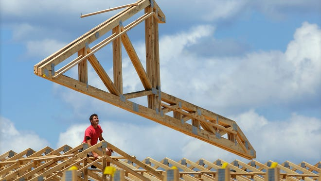 Construction workers build a commercial complex in Springfield, Ill.