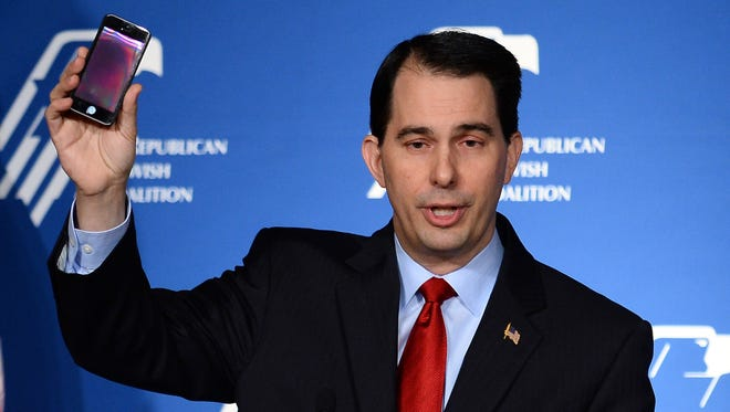 LAS VEGAS, NV - MARCH 29:  Wisconsin Gov. Scott Walker holds up his cell phone as he speaks during the Republican Jewish Coalition spring leadership meeting at The Venetian Las Vegas on March 29, 2014 in Las Vegas, Nevada. The Republican Jewish Coalition began its annual meeting wtih potential Republican presidential candidates in attendence, along with Republican super donor Sheldon Adelson. (Photo by Ethan Miller/Getty Images)