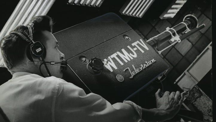 A camera operator aims a then-new television camera