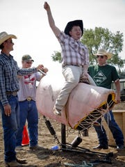 Jon Hargett rides a mechanical bull while assisted