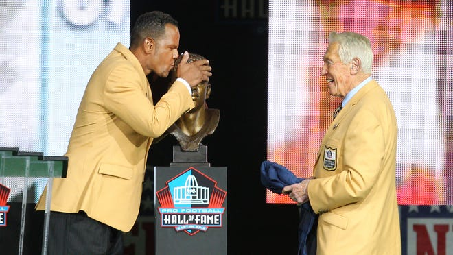 Andre Reed kisses his Hall of Fame bust after being presented by Marv Levy on Saturday night in Canton, Ohio.
