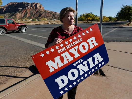 Donia Jessop holds her mayoral campaign sign outside her store in Colorado City, Ariz. on Oct. 26, 2017.