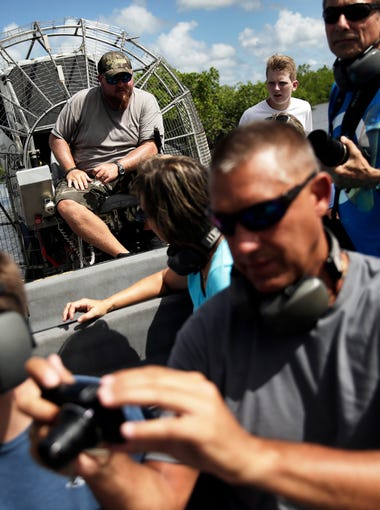 People take photos of an alligator in the water while on an airboat ride captained by Carl Nicholson at Wooten's Everglades Airboat Tours in Ochopee on Wednesday, July 20, 2016. Nicholson manages Wooten's.