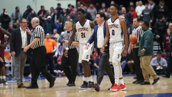 Stepinac head coach Pat Massaroni, center, walks Adrian Griffin Jr. (21) and Alan Griffin (0) off the court during the Crusader Classic at the Westchester County Center on Jan. 5, 2018.
