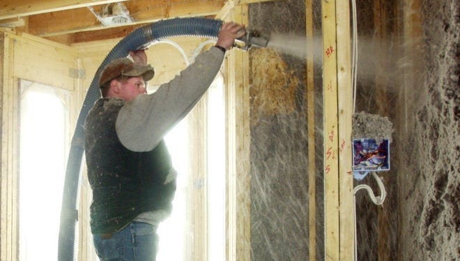 A worker blows insulation into the walls of a home. Homes lose about 9 percent of heat through the walls, 21 percent through the doors and windows and 70 percent through the roof.