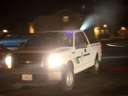 A crew with the Coachella Valley Mosquito and Vector Control District sprays for an invasive mosquito in a Cathedral City neighborhood early Thursday morning, September 22, 2016.