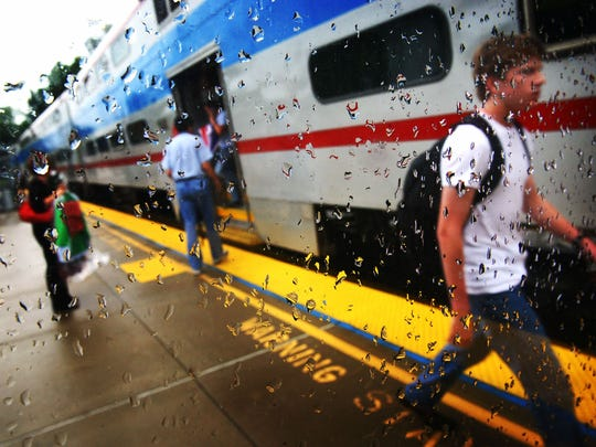 Commuters on the Music City Star disembark at the Donelson Station during the evening rush hour after rain had swept through the area.