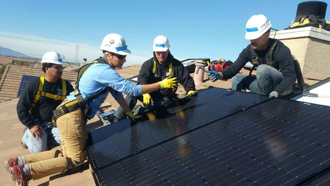 Solar Corps Construction Fellow Lisa Ricci helps Rancho Cielo Construction Academy students Rudy Treveno, Samuel Arevalo and Josiah Drummondo work on installing solar panels at a Soledad home on Friday.