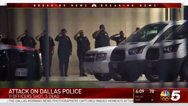 In this still image from video provided by NBC DFW, police officers salute their fallen peers outside Parkland Memorial Hospital in Dallas, where several officers were transported after shootings at a protest late Thursday, July 7, 2016. Five Dallas police officers were fatally shot, raising the total number of police killed by firearms nationally to 26, 44% higher than at this time last year.