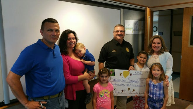 Samantha Schneider asked for donations for the Springfield Police Foundation instead of birthday presents. Pictured (from left) are her parents, Donna and Dan; younger siblings, Charlie and Jessica; Chief Paul Williams; Samantha Schneider; foundation president Betsy Miller; and Samantha's friend, Journey.
