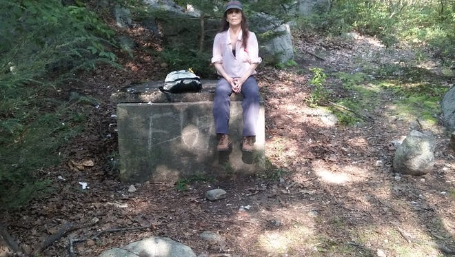 In this Aug. 21 photo, Marilyn Piscitelli sits atop a cistern that had been covered with trash during an Aug. 11 visit.