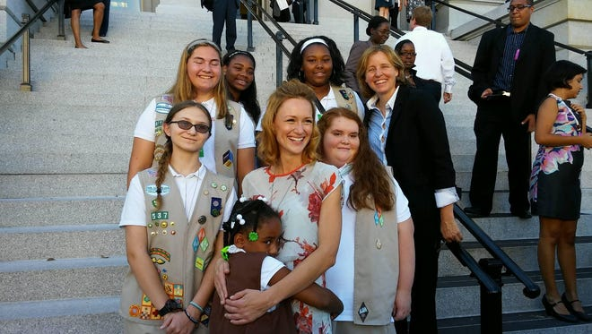 Outside the White House in Washington, D.C., local Girl Scouts take a picture with actress Kerry Bishe (center) and U.S. Chief Technology Officer Megan Smith (right).