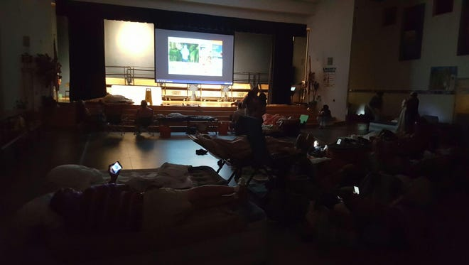 Shelter residents watched live storm coverage as they rested and waited for the storm to pass