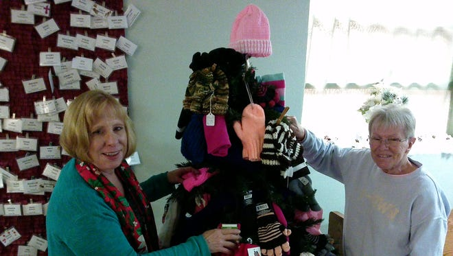 Rev. Janet Clark, left, pastor of Fairview United Methodist Church, and church member Susan Barton with knitted mittens, hats and socks for students at Calvin Coolidge School.