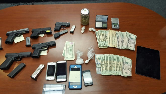 Henderson police display guns, drugs, money and other items seized in a drug sweep Monday night.