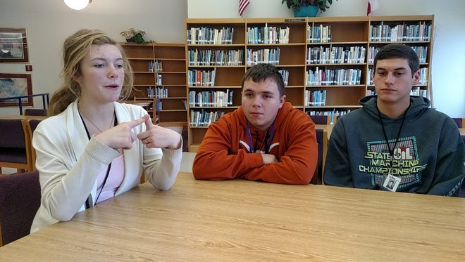 Kathlyn Messer, a sophomore at Wylie High School, discusses a new business that she and four classmates are starting after taking an entrepreneurship class. Ben Hudman and Brandon Lovett, both juniors and part of the team, listen as Messer explains the business, which will cater to the Wylie district for services such as finding a baby sitter.
