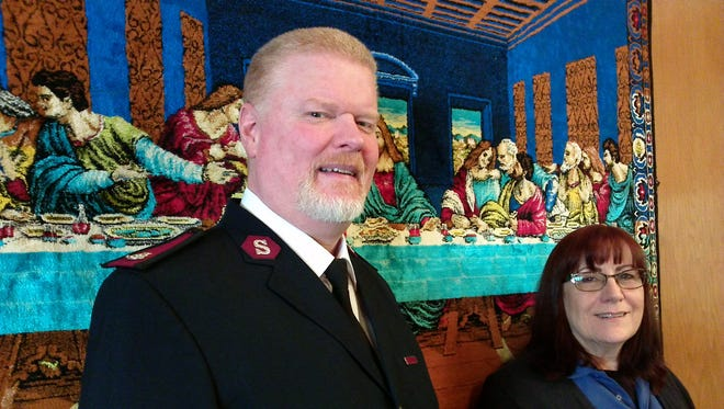 Maj. Timothy MacLean and Counselor Theresa Tague in front of Last Supper tapestry in the chapel of the Salvation Army Adult Rehabilitation Center.