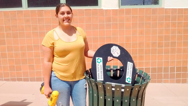 Danielle Diaz, Intern in the Office of Sustainability, completes installation of a new green recycling bin on Broadway in front of the Murray Hotel.