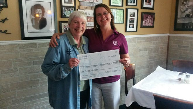 Cheatham County Lions Club member Tina Tosten presents Kathryn Mitchem with a check for $500.