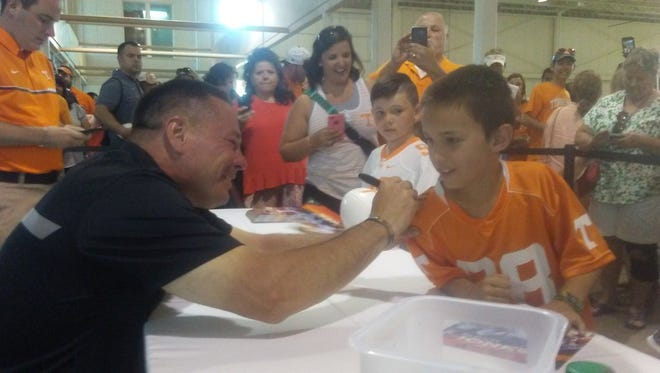 Vols football coach Butch Jones signs the jersey of Bo Dylan Anderson, 9, during a Big Orange Caravan event in Memphis on June 11.