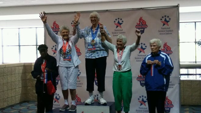 Violet Halvorson, center, is shown at the National Senior Games where she won a gold medal in the shuffleboard competition for her age division.