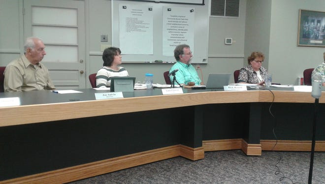 Highland Township board members watch a presentation on sewers.