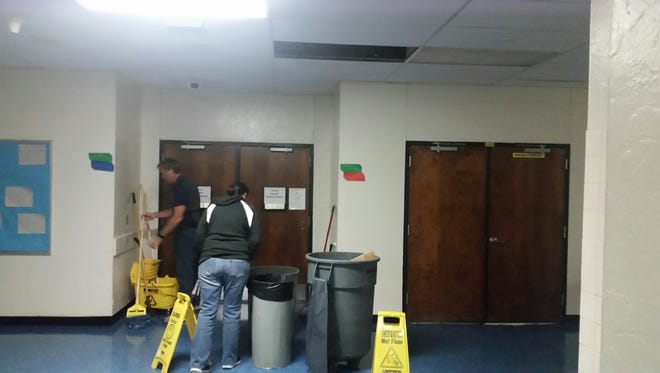 St. Lucie County school staff mop the water that fell on the floor from a roof leak at Lakewood Park Elementary School on Indrio Road in northern St. Lucie County.  No one was injured. And almost all of the 114 people inside the shelter slept through it.