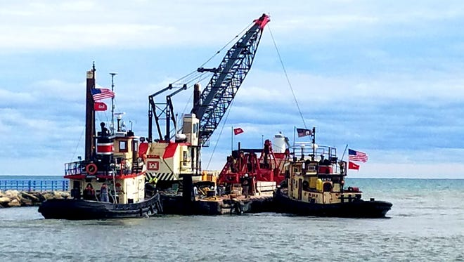 Pictured, U.S. Army Corps of Engineers personnel and equipment from Kewaunee are mobilized at Two Rivers' Lake Michigan harbor to undertake emergency repairs to the south breakwater.