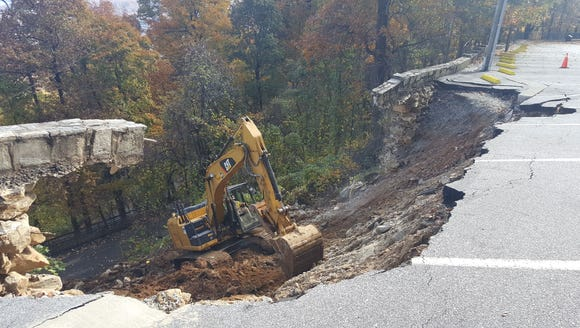 A worker uses a track excavator to remove debris and clear the collapsed wall and the area below it at Chimney Rock State Park.