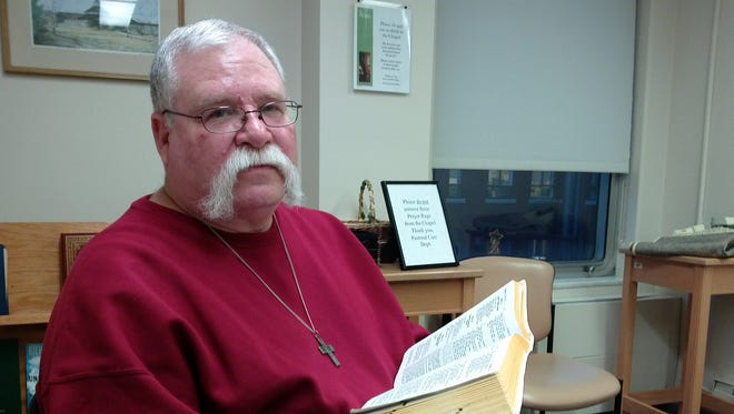 Al Babicek, lay volunteer, Broome County Council of Churches Hospital Chaplaincy program, with Bible inside the Chapel at Wilson Hospital.