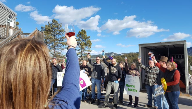 Staff at Prairie Berry Winery in Hill City toast the first shipment of the winery's wines to a distributor in North Dakota.