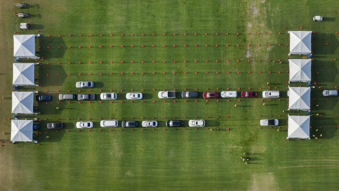 People wait in their cars to be tested for COVID-19  at a drive-through coronavirus testing location at the FITTEAM Ballpark of The Palm Beaches on March 31, 2020 in West Palm Beach, Florida.