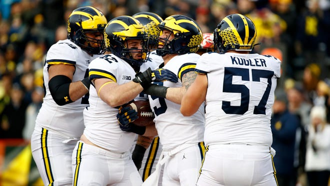 Michigan fullback Henry Poggi, second from right, celebrates his touchdown with teammates in the first half of U-M's win on Saturday in College Park, Md.