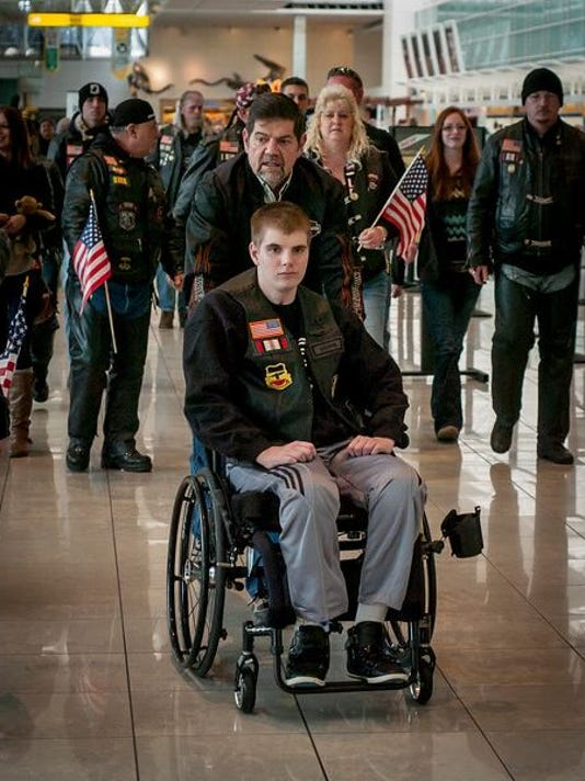 Cpl Matthew Hanes and his family, mother Chris and father Lee, are escorted by members of the Warrior Brotherhood after arriving at BWI Airport, Wednesday March 13, 2013. Cpl Hanes was returning home after being wounded while deployed in Afghanistan in 2012 and spending the next several months in a specialized rehab facility in Florida.