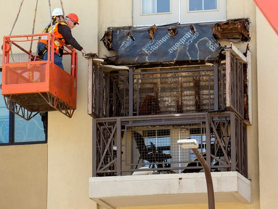 Workers examine a balcony that collapsed in Berkeley,