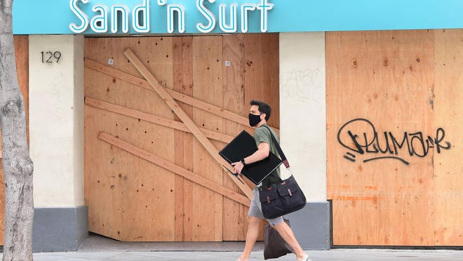 A man walks past a closed Sand 'n Surf shop as many business establishments remain boarded up around Santa Monica's Third Street Promenade shopping district on June 26, 2020 in Santa Monica, Ca.