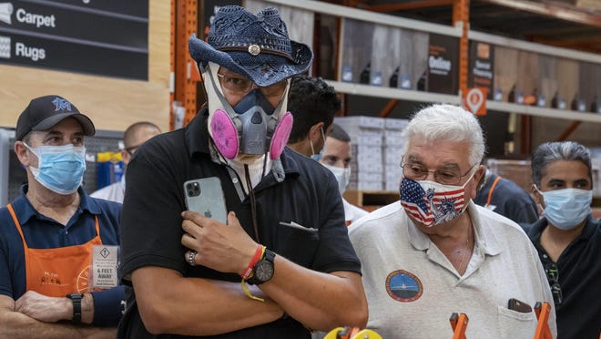 Masked workers and customers listen to Gov. Ron DeSantis Friday at a news conference to promote the sales tax holiday and encourage people to prepare for the hurricane season at a Home Depot west of Boca Raton.