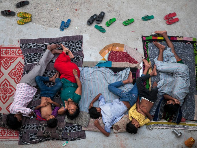 An Indian family sleeps on the roof of a house to beat