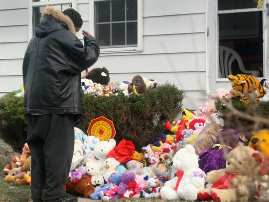 Demiris Kerr crosses himself as he pays his respects at the 3283 Hovey Street house.