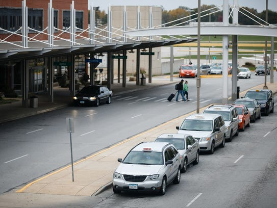 Taxis line up and wait for their next fare at the Des