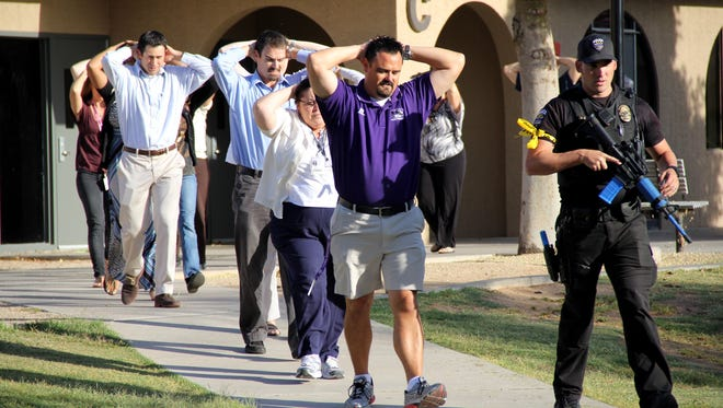Goodyear police officers participate in a mock active-shooter drill with staff at Millennium High School in Goodyear in April. Training helps police review emergency-response plans.
