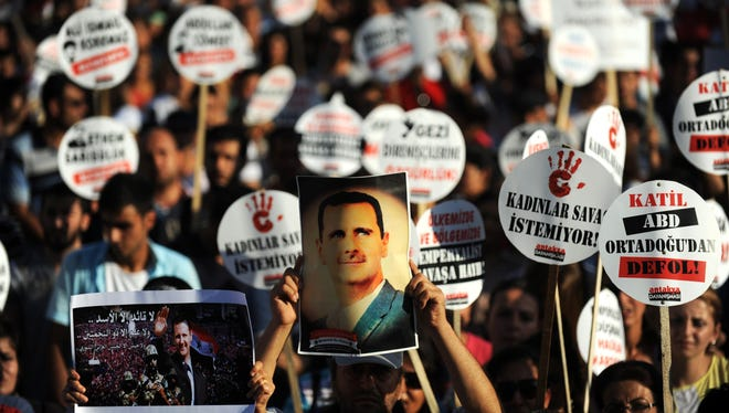 A protester holds a portrait of Syrian President Bashar al-Assad during a rally on September 1, 2013, in Hatay against a possible attack on Syria in response to alleged use of chemical weapons by the Assad government.
