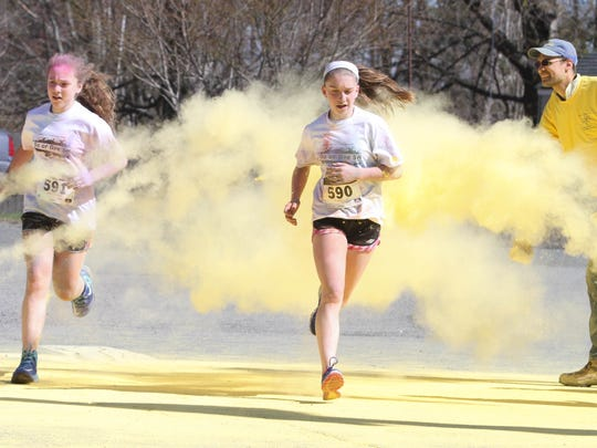 Runners get splattered with yellow during the Do or Dye 5K, a color run for the American Cancer Society, at Turkey Brook Park in Budd Lake on April 25, 2015.