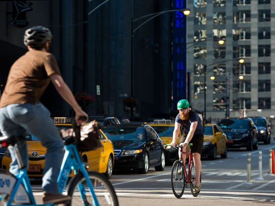 A cyclist travels north across Kinzie Street on Dearborn