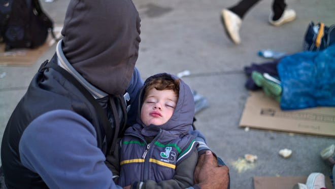 A Syrian refugee man holding his sleeping son, rests on the ground after spending the night at a collection point in the truck parking lot of the former border station on the Austrian side of the Hungarian-Austrian border near Nickelsdorf, Austria, Wednesday, Sept. 23, 2015.